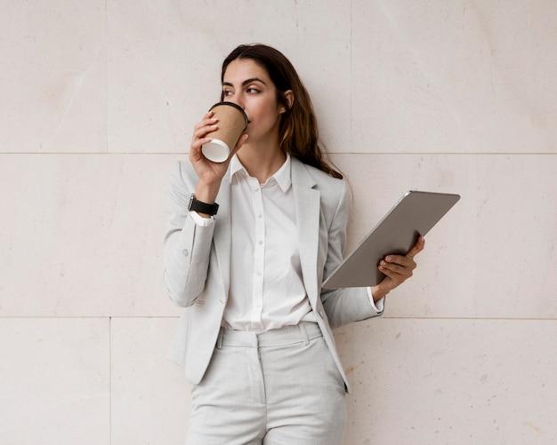 Элегантная деловая женщина пьет кофе, держа планшет