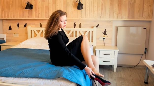 Элегантная деловая женщина в черном платье сидит на кровати и снимает туфли на каблуках