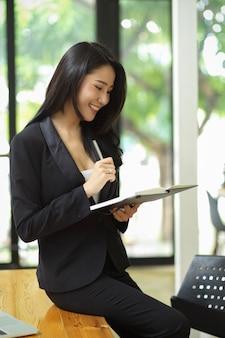 검은 양복을 입은 우아한 여성 사업가가 사무실에서 플래너 책을 들고 책상에 기대어 서 있다