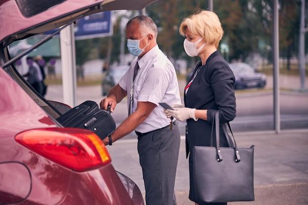 신사가 자동차 트렁크에 여행 가방을 배치하는 동안 티켓과 여권을 들고 의료 마스크에 우아한 사업가