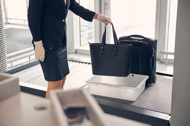 手荷物管理手順とセキュリティチェックのために荷物を準備する滅菌手袋のエレガントな実業家
