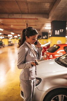 지하 주차장에서 열쇠로 차를 잠그는 우아한 사업가입니다.