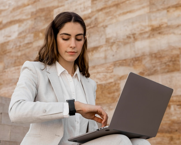 Elegante imprenditrice guardando smartwatch e lavorando su laptop all'aperto