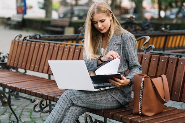 Elegant businesswoman sitting on bench