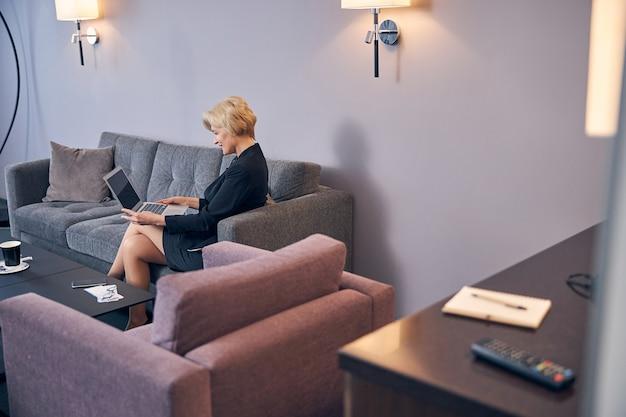 Элегантная деловая женщина сидит на диване и работает над современным ноутбуком