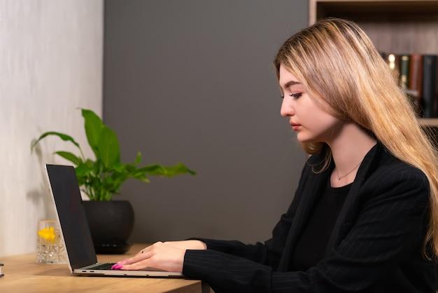 Элегантная деловая женщина сидит за своим портативным компьютером за столом в офисе, вид сбоку, концентрируясь на своей работе