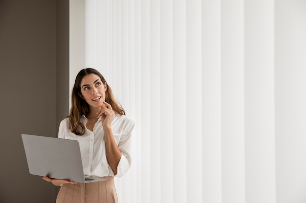 Elegant businesswoman using laptop with copy space