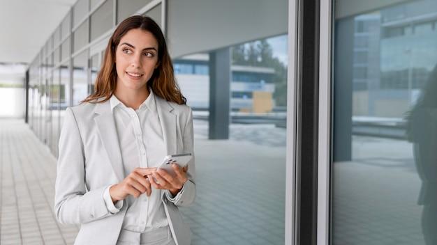 Elegante imprenditrice utilizza lo smartphone all'aperto con copia spazio