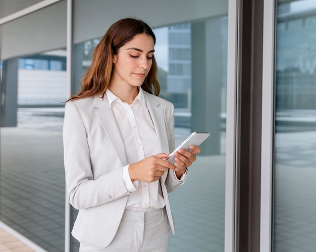 Elegante imprenditrice utilizza lo smartphone all'aperto