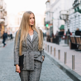Elegant businesswoman walking in city with clipboard