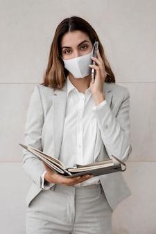 Elegante imprenditrice con maschera parlando al telefono
