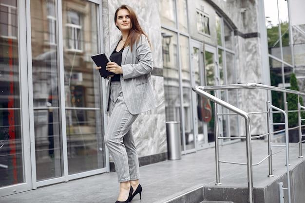 La donna di affari elegante che lavora in una città e usa il taccuino