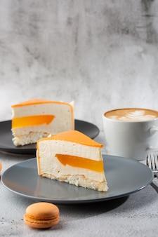 코코넛, 열정 과일, 망고 및 바나나가 들어간 우아한 케이크로 초콜릿 글레이즈로 덮여 있습니다. 대리석 백그라운드에 오렌지 계층화 된 케이크의 조각입니다. 생과자 카페 또는 카페 메뉴 배경 화면. 세로.