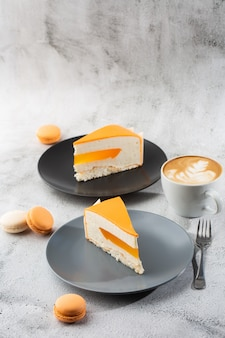 Elegant cake with coconut, passion fruit, mangoes and bananas, covered with chocolate glaze. slice of orange layered cake on marble background. wallpaper for pastry cafe or cafe menu. vertical.