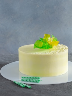 Elegant cake with yellow, green flowers decoration and birthday candles on grey