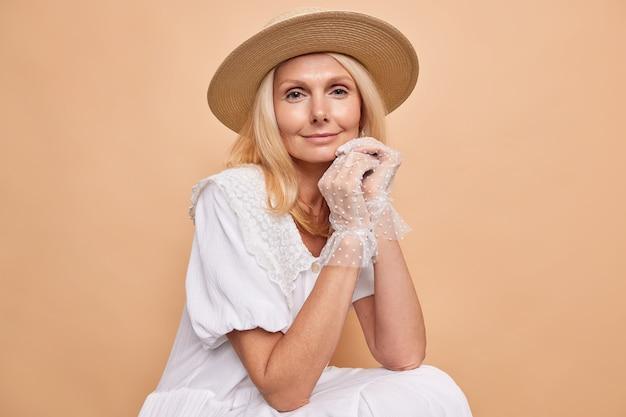 Elegant calm blonde woman sits against beige wall listens something attentively wears white stylish dress fedora and lace gloves looks with serious expression at front