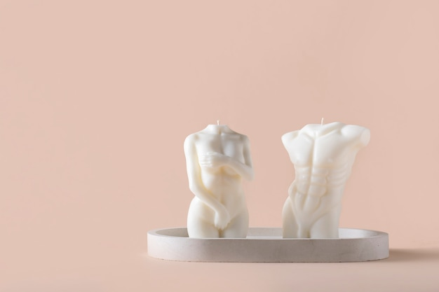 Elegant candles in the shape of a male and female body on a concrete stand on a beige background