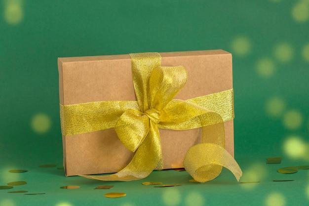 金色のボケ味と緑の背景に金色のリボンとエレガントな段ボールのギフトボックス