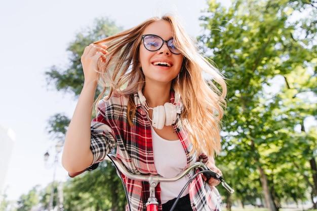 公園で楽しんでいるエレガントなのんきな女の子。晴れた日を楽しんでいる感情的な金髪の女性モデル。