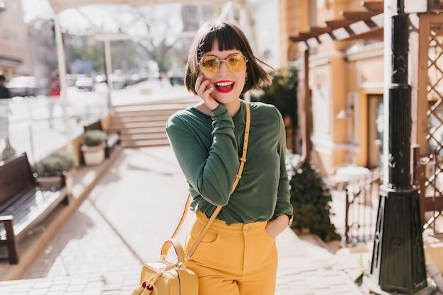 都会の春の日に幸せを表現するサングラスでエレガントな白人の女の子。笑っている黄色のハンドバッグと素敵な女性モデルの屋外写真