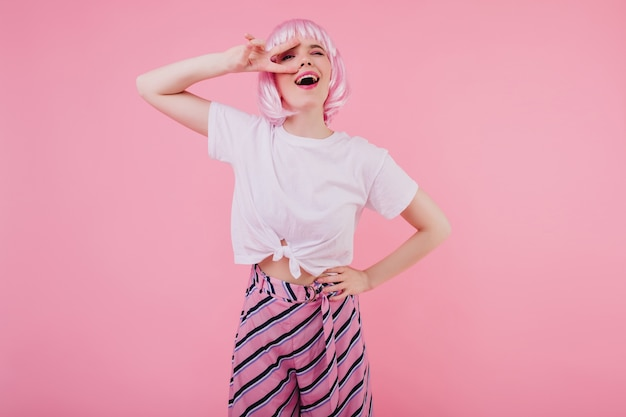 Элегантная кавказская девушка с розовыми волосами смеется на яркой стене. беззаботная европейская дама в великолепном наряде