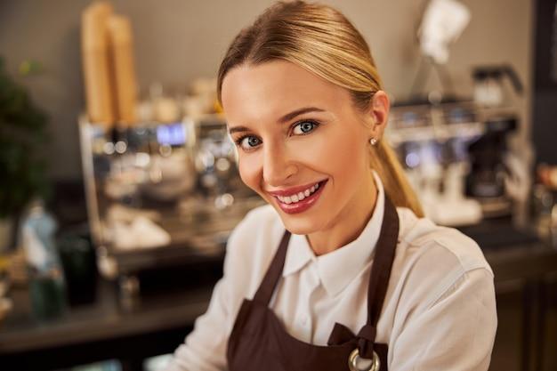 카페에서 사진 카메라를 보고 웃고 있는 우아한 백인 여성