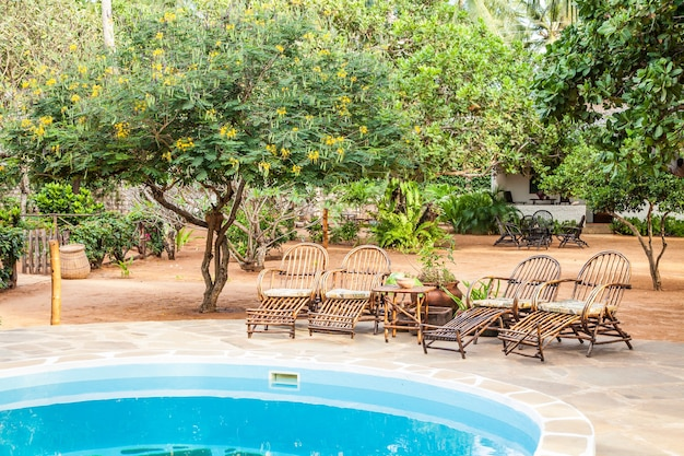 ケニアの庭の中のプールの近くにある木で作られたエレガントな椅子