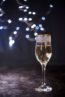Elegant champagne glass on textured surface at night party