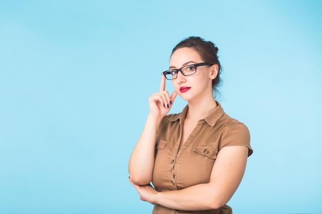 Элегантная жизнерадостная брюнетка в очках, улыбаясь в камеру на синей стене с копией пространства