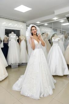 Элегантная жизнерадостная дама в свадебном платье стоит в свадебном салоне