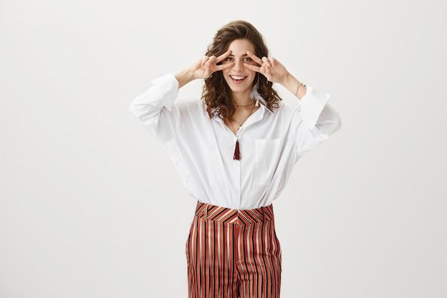 ピースサインを見せて笑顔のエレガントな陽気な女性