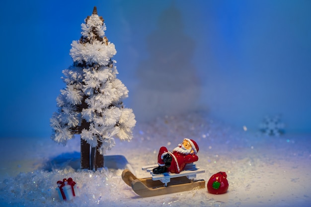 Elegant classic christmas composition with christmas tree made of crystals and santa claus on a white sleigh and gifts