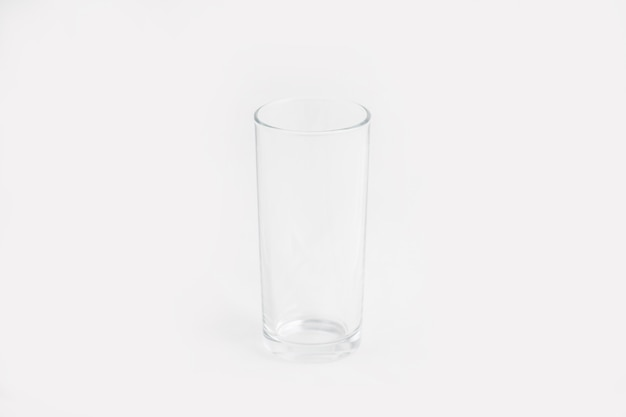 Elegant clear glass cup isolated on a white wall