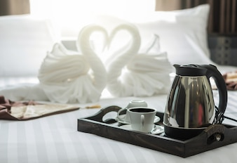 Elegant coffee cup set on wooden trey in modern bedroom interior with blurred background of two nice