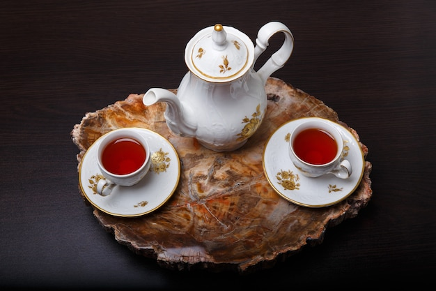 Elegant coffee set on an exclusive tray made from a cut of ancient petrified wood. top view.