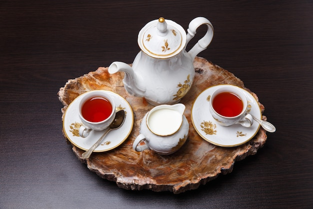 Elegant coffee set on an exclusive tray made from a cut of ancient petrified wood