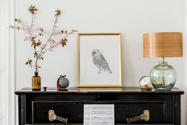 黒のピアノ、ゴールドのモックアップポスターフレーム、春の花、装飾、ランプ、モダンな家の装飾のスタイリッシュなプレソナルアクセサリーを備えたリビングルームのインテリアのエレガントな構成。