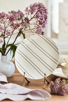 素朴なテーブル、美しい磁器、花、キッチンアクセサリーを備えた上品なダイニングルームのインテリアデザインのエレガントな構成。細部の美しさ。レンプレート。