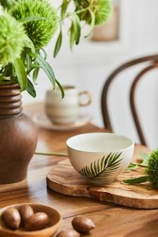 소박한 테이블, 아름다운 도자기, 꽃 및 주방 액세서리를 갖춘 고급스러운 식당 인테리어 디자인의 우아한 구성. 디테일의 아름다움. 주형.