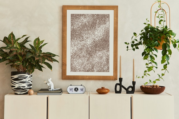 모의 포스터 프레임, 베이지색 사이드보드, 식물 및 빈티지 개인 액세서리가 있는 세련된 거실 내부의 우아한 구성. 공간을 복사합니다. 주형.