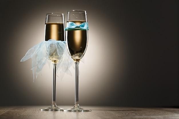 シャンパンを着た青い新郎の蝶ネクタイと花嫁のベールのエレガントな概念的な2杯
