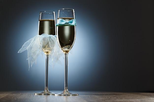 青い新郎の蝶ネクタイと花嫁のベールに身を包んだ新婚旅行者のためのエレガントな概念的な2杯のシャンパン。明るいお祭りの青い背景の画像