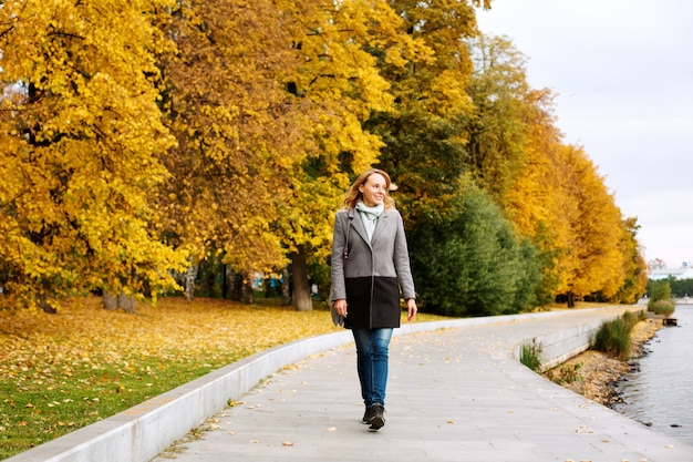 Elegant confident woman walking along the river in city park and smiling