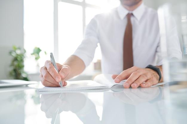 エレガントな現代的なビジネスマンが職場でブレーンストーミングしながらコピーブックで作業ノートを作成