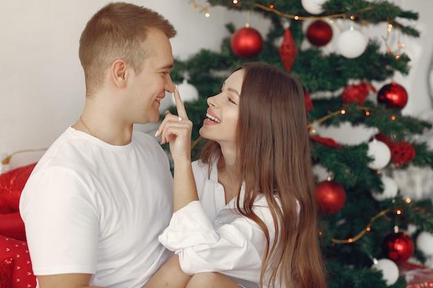クリスマスツリーの近くの自宅でエレガントなカップル