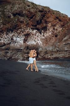Elegant couple on a beach near rocks