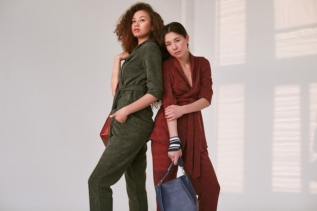 Elegant couple of black and asian women in fashionable green and red suits