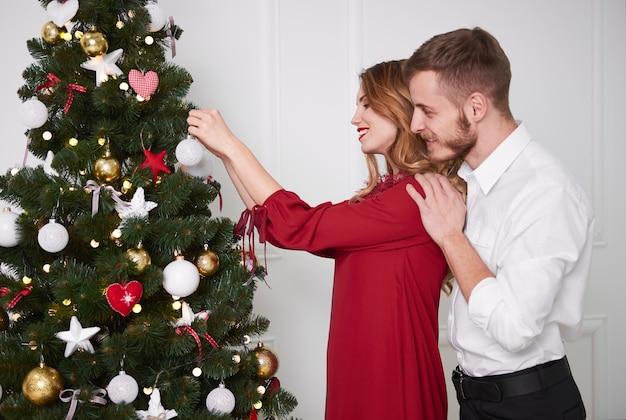 クリスマスツリーを飾るエレガントなカップル