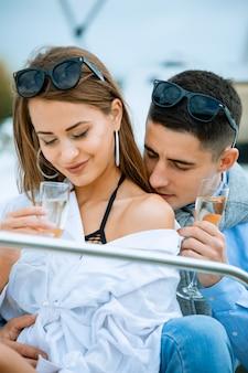 愛のエレガントなカップル。ガラスのシャンパンジーで豪華な女性の肩にキスする金持ちの清楚な男。ボートでロマンチックなデート。ヴァカンティオンのコンセプトです。