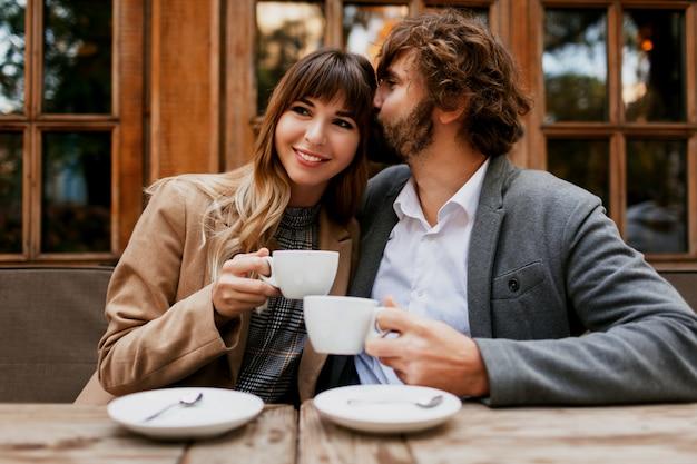 Элегантная влюбленная пара сидит в кафе, пьет кофе, разговаривает и наслаждается временем, проводимым друг с другом. селективный акцент на чашке.